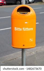 """Berlin, Berlin/Germany - 23.03.2019: A garbage can with ashtray of the Berliner Stadtreinigung with the funny slogan """"Please feed"""" on the roadside."""