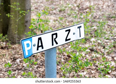 Berlin, Berlin/Germany - 24.03.2019: A sign for a parking lot on the doctor stands. The sign is dented and as big as a license plate of the car.