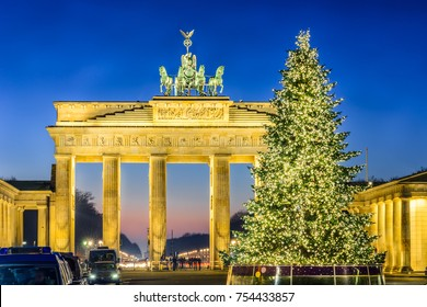 Berlin Brandenburg Gate (Brandenburger Tor) golden illuminated with the  Christmas Tree in front and during Christmas and New Year at twilight with Siegessaule (Siegessaeule) behind.