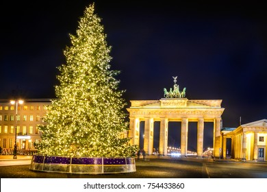 Berlin Brandenburg Gate (Brandenburger Tor) golden illuminated with a big Christmas Tree during Christmas and New Year at night