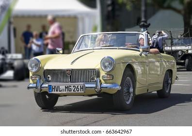 BERLIN CLASSIC CAR SHOW – JUNE 18, 2017: Folks driving a classic yellow MG cabriolet car