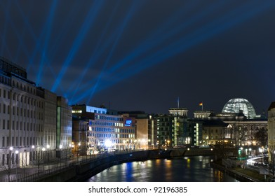 BERLIN - DECEMBER 30: Reichstag, the river Spree and the rays of the searchlight in the night sky, on December 30, 2011 in Berlin, Germany. The Reichstag building is a historical edifice in Berlin.