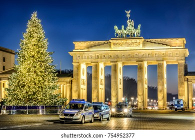 BERLIN , DECEMBER 5, 2016, Brandenburg Gate (Brandenburger Tor) golden illuminated with Christmas Tree and german police patrolling during Christmas and New Year at sun set twilight in Berlin, Germany