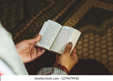 Berlin, German - August 2018: Young muslim woman reading the Quran in the mosque with a carpet in the background