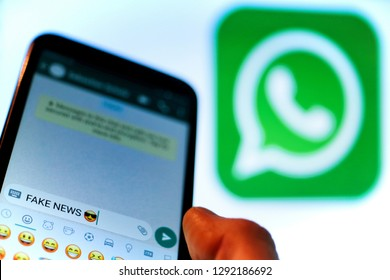 Berlin, Germany - 01/22/2019 Macro image close up of a thumb finger on mobile smartphone screen texting fake news into Whats App account. Whats App rolls out changes to curb spread of misinformation