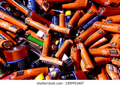 Berlin, Germany 02/09/2019 Orange, blue closeup detail of large pile of dead used single use disposable alkaline batteries of various manufacturers mainly AA and AAA. Energy source, recycle concept