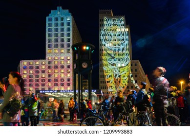Berlin, Germany - 05 OCTOBER 2018: Night atmosphere of crowd enjoy event Festival of Lights, Berlin leuchtet, the projection mapping lighting art on tower around Potsdamer Platz during the night.