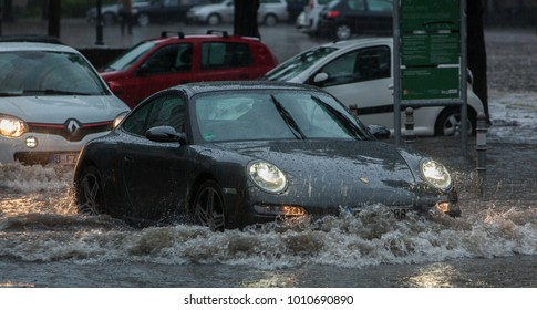 Berlin, Germany - 06 29 2017: Cars driving through Water in Berlin Streets, flooded after Days of heavy Rainfalls