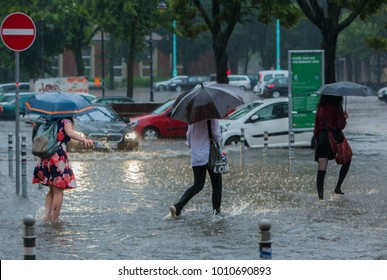 Berlin, Germany - 06 29 2017: Three Women with Umbrellas walking through Water in Berlin Streets, flooded after Days of heavy Rainfalls