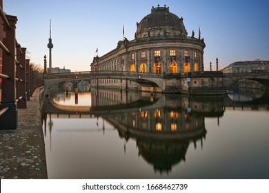 Berlin, Germany, 06.03.2020: Museum Island on Spree river and TV tower in the background at sunrise, Bode-Museum, cityscape early in the morning, reflections in the water, beautiful blue sky at dusk