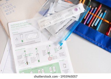 Berlin, Germany - 14th April 2021: SARS-CoV-2 Rapid Antigen Test, self test with school equipment (pencil case and math book)