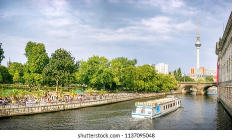 BERLIN, GERMANY - 17 Jul 2018: View of the Spree and boats, Monbijou Park with its dancing and cafe area at the embankment and other Berlin sights from the Monbijou bridge
