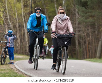 Berlin, Germany. 20. April. 2020. Coronavirus. Crowd of masked bicycle riders ride in a park on a bike path. Allowed to walk in the parks on the beaches and keep their distance during the epidemic.