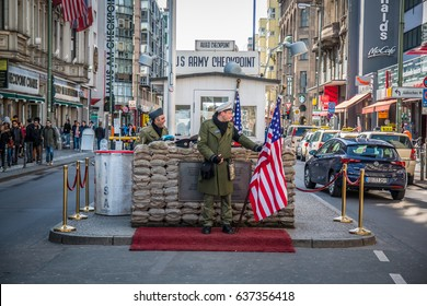 BERLIN ,GERMANY- 20 MARCH 2017  Checkpoint Charlie, on March 20, 2017 famous passage between the West and East Berlin during the Cold War.  American soldier standing guard holding the EE.UU. flag.