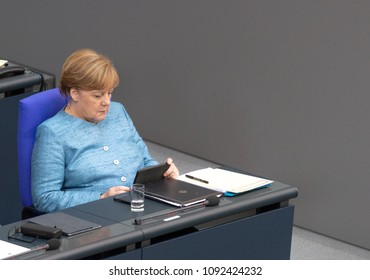 Berlin, Germany, 2018-05-16:  German Chancellor Angela Merkel looks at her tablet during the debate about the federal budget 2018 at the German Bundestag in Berlin
