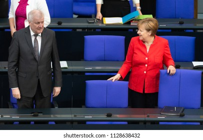 Berlin, Germany, 2018-07-04: Debate about the federal budget - Chancellor Angela Merkel and German Minister for the Interior, Horst Seehofer, arrive  at the German Bundestag in Berlin