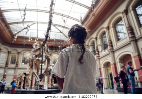 Berlin, Germany / 23.08.2018 : A family goes to see the archeology museum where prehistoric dinosaur skeletons are present. Concept of: educational, family, school, history.
