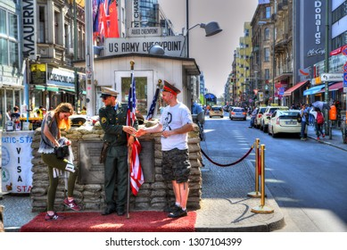 BERLIN GERMANY APR 19: Soldiers with uniform at Checkpoint Charlie, on in Berlin. Tourists taking photo at Checkpoint Charlie - the famous passage between the West and East Berlin during the Cold War.