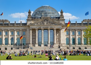 BERLIN, GERMANY - APR 28, 2018: People relaxing on the grass in front of the Reichstag building, seat of the German Parliament (Deutscher Bundestag).