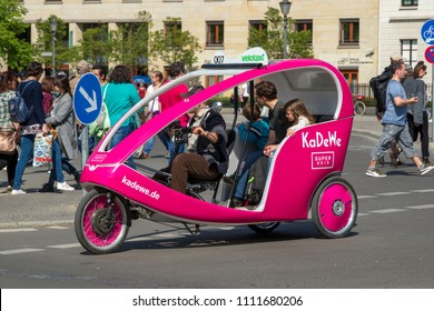 BERLIN, GERMANY - APR 28, 2018: Velotaxi bike taxi with customers cycling through the streets of Berlin.