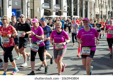 Berlin, Germany - April 08, 2018: Elderly women in pink t-shirts among other people running on the Unter den Linden Street during the 38th edition of the biggest German half marathon