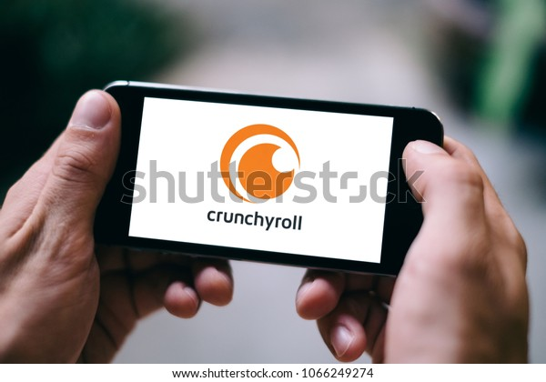 BERLIN, GERMANY - APRIL 08, 2018: Closeup of iPhone screen with white CRUNCHYROLL APP LOGO and ICON