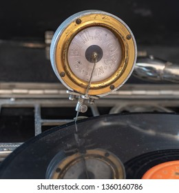 Berlin, Germany - April 1, 2019: Pickup decorated with the name of the manufacturer of a portable gramophone from Germany in the 1920s with a shellac disc and reflection of the pickup.