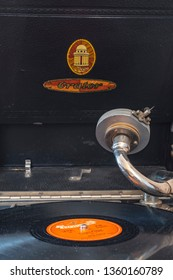 Berlin, Germany - April 1, 2019: Pickup of a gramophone from Germany in the twenties with a shellac disc in the foreground and the logo of the company Odeon in the background.