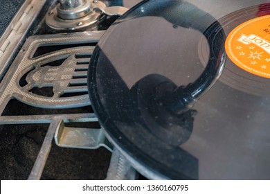 Berlin, Germany - April 1, 2019: Integrated horn of a historic record player (gramophone) from Germany in the in the 1920's with a shellac disc and the reflection of the pickup.