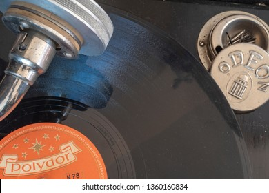 Berlin, Germany - April 1, 2019: Historic shellac disc by Polydor with a part of the pickup and a box for the plate needles of an old gramophone from the company Odeon from Germany in the 1920s.