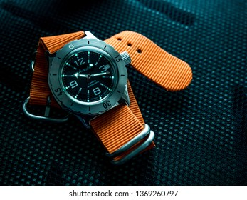 BERLIN, GERMANY - APRIL 1, 2019: Vostok Amphibia 100315 Diver watch with orange nylon strap and new bezel on back of backpack