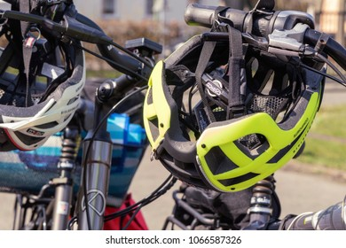 Berlin, Germany - April 10, 2018: Close-up of yellow and white bicycle helmets hanging on the handlebars of bicycles