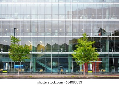 Berlin, Germany - April 12, 2017: Multistory glass office building and green trees in the foreground.