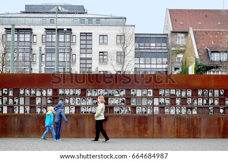Berlin, Germany - April 12, 2017: Monument of the Berlin Wall with photos of people and visitors.