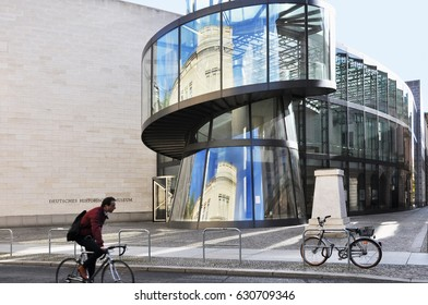 Berlin, Germany - April 13, 2017: German Historical Museum in Berlin. A riding bicyclist in the foreground.