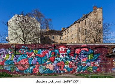 Berlin, Germany - April 14, 2015. Not renovated house in the district of Berlin-Friedrichshain behind a wall with graffiti.