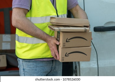 Berlin, Germany - April 18, 2018: Cropped image of an Amazon Prime delivery man during a work shift. Amazon is an American electronic online commerce company