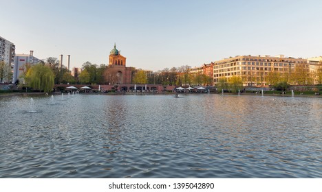 BERLIN, GERMANY - APRIL 18, 2019: People have a rest near Engelbecken or Angel fountain and St. Michael Church at spring. Berlin is the capital and largest city of Germany by both area and population.