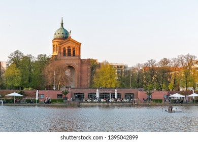 BERLIN, GERMANY - APRIL 18, 2019: People have a rest near Engelbecken o Angel fountain and St. Michael's Church at spring. Berlin is the capital and largest city of Germany by both area and population