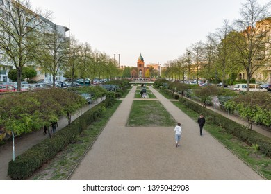 BERLIN, GERMANY - APRIL 18, 2019: People walk in a park in front of Angel pond and St. Michael's Church at spring. Berlin is the capital and largest city of Germany by both area and population.