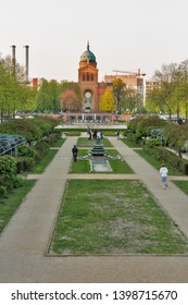 BERLIN, GERMANY - APRIL 18, 2019: People walk in a park with Engelbecken or Angel pond and St. Michael's Church at spring. Berlin is the capital and largest city of Germany by both area and population