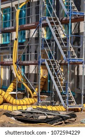 Berlin, Germany - April 2, 2018: New construction on a construction site with scaffolding, hoses, ladders and various materials