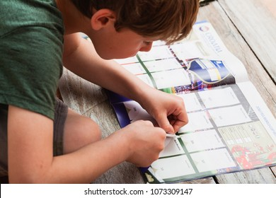 BERLIN, GERMANY - APRIL 20, 2018: Seven year old boy pasting stickers into the Panini collection album for the football/soccer world championship in Russia 2018.