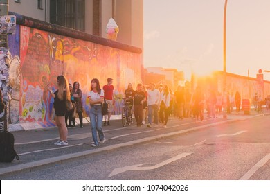 Berlin, Germany - april 2018: Young people walking at Berlin wall ( East Side Gallery) on summer day evening with sunset sky