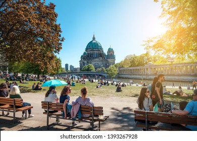 Berlin, Germany - April, 2019: People in public park on a sunny day near Museum Island and Berlin Cathedral