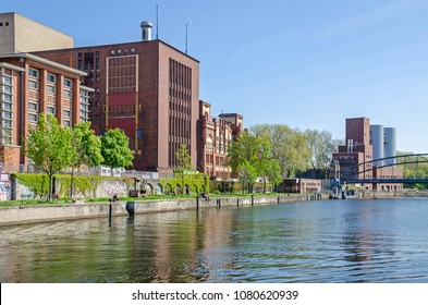 Berlin, Germany - April 22, 2018: Cogeneration plant Charlottenburg operated by Vattenfall with its Brick Gothic historic machine hall and a part of the bridge Siemenssteg  as seen from the Spree