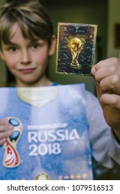 BERLIN, GERMANY - APRIL 28, 2018: Boy holding official trophy card of official FIFA licensed Panini collectibles sticker and album for the football world cup 2018 in Russia.