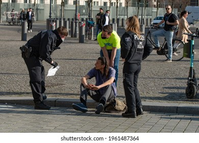 Berlin, Germany - April 3rd 2021: Protester at an anti-corona demo being checked by police officer during a demonstration at Brandenburger Tor.