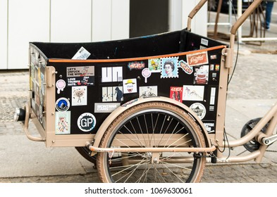 Berlin, Germany - April 5th, 2018: Bicycle with front trailer with assorted stickers.