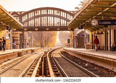 Berlin, Germany - April 6, 2019: View along the tracks in the S-Bahn station Buckower Chaussee in Berlin, Marienfelde. The atmosphere is determined by the orange sunlight on a hazy day.